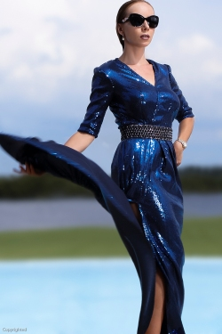 Blue sequins dress with high slit .